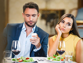 Man checking smartphone on date