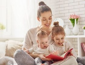 Young mum reading to her babies