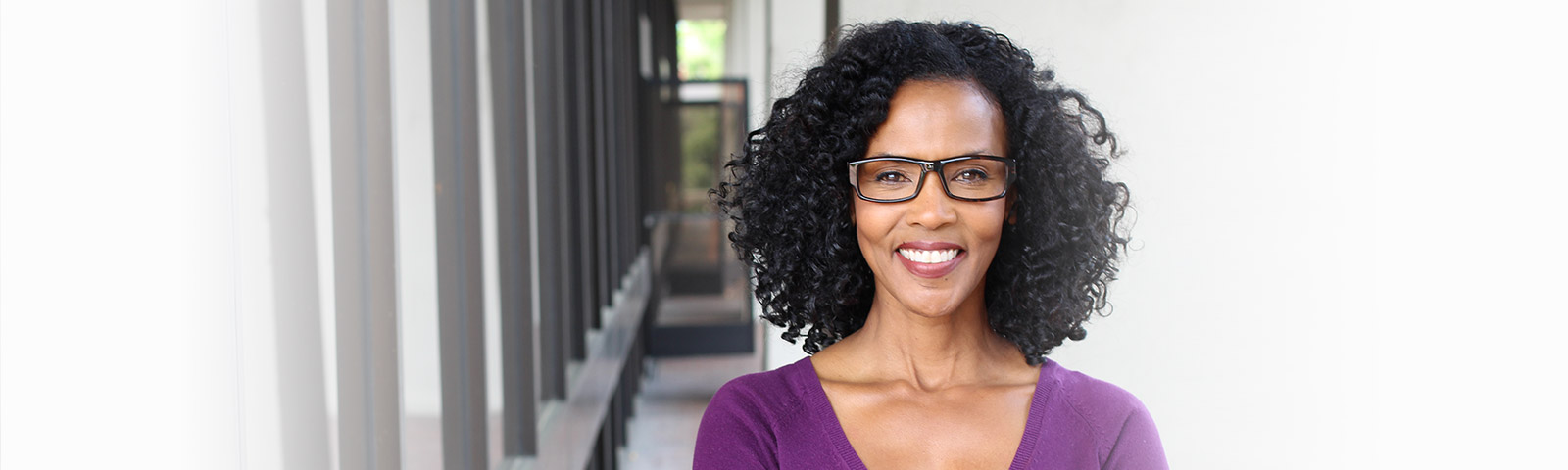 black woman with glasses smiling