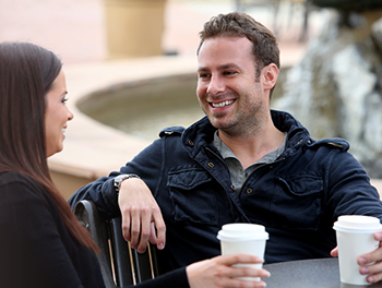 man and woman drinking coffee outside smiling