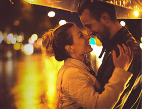 couple embracing in the rain under an umbrella