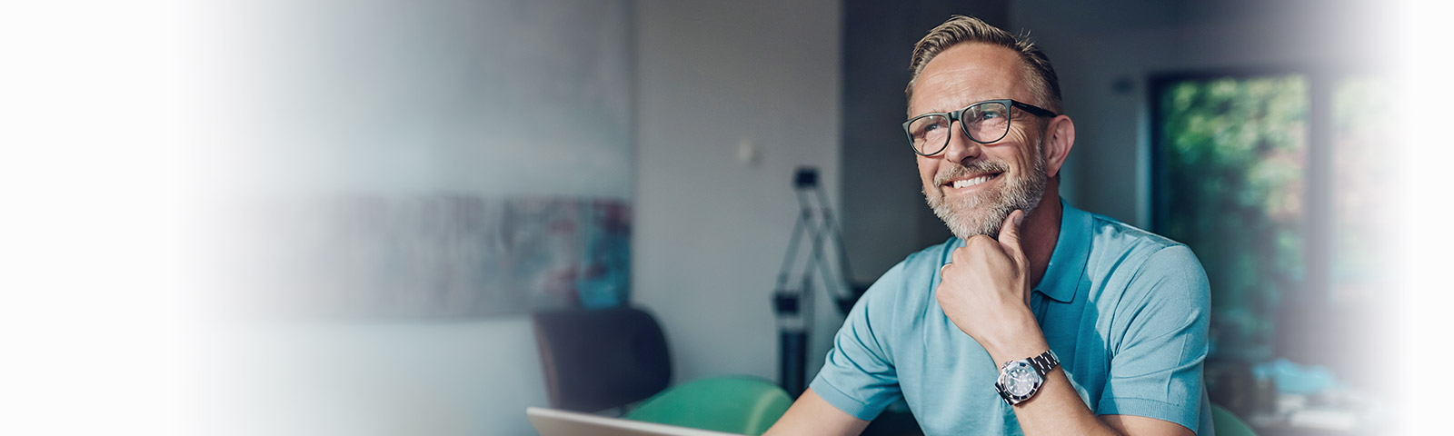 man with glasses smiling using computer