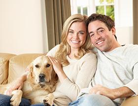 catholic couple with dog smiling
