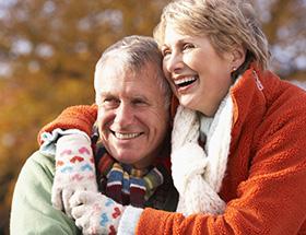 older couple hugging outside