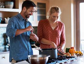 vegan couple preparing dinner in kitchen
