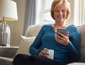 older woman on sofa looking at phone