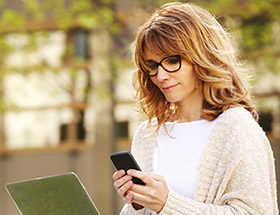 woman in glasses using smart phone