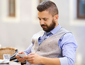 exclusive man looking at smart phone at cafe
