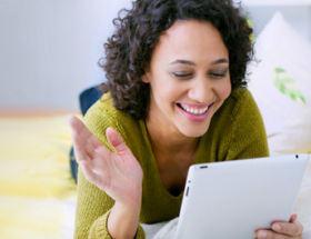 curly haired Australian woman sending online dating messages from her tablet