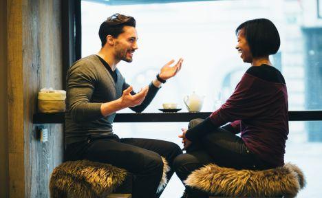 man joyously mansplains to woman in cafe