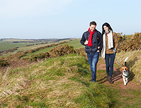 smiling couple walk dog in countryside