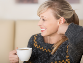 Pretty blonde woman with on sofa with a cup of coffee